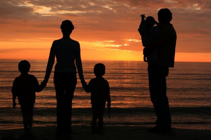Young family watching sunset over the ocean